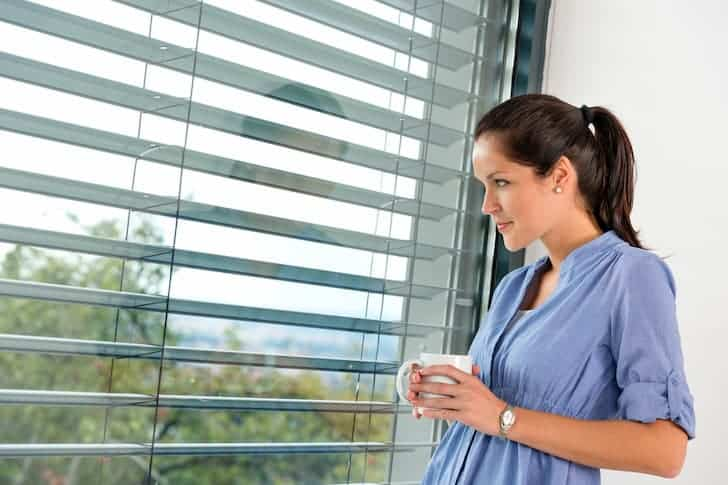 young-woman-day-dreaming-window-blinds