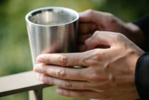 person-holding-steel-cup